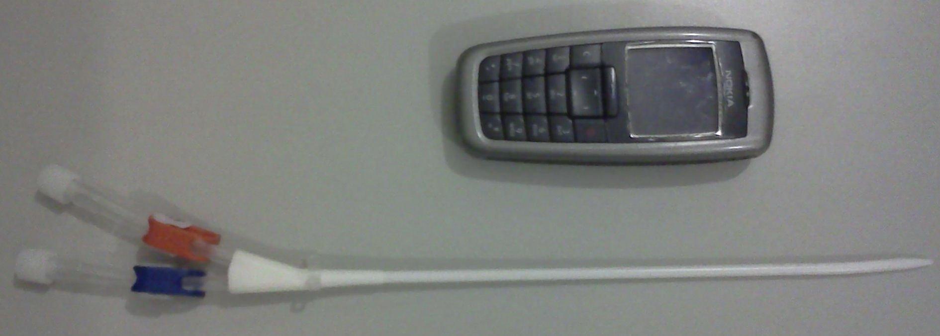 Cateter venoso central na veia jugular (telefone para comparação de tamanho)